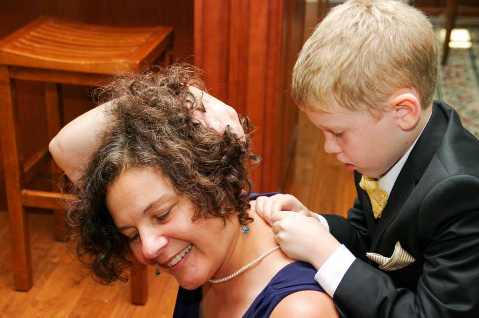 "Little Patrick putting my mother's ""pearls"" on me so I can bring her to the ceremony with me!"